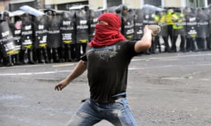 Demonstrators clash with riot police during a protest in Quito against the constitutional amendment allowing indefinite re-election of the president.