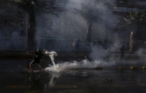 A demonstrator returns a teargas canister fired by police during a protest against police after a video surfaced that appeared to show an officer pushing a youth off a bridge at a demonstration in Santiago.