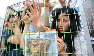 Animal rights activists lie in cages as part of a demonstration against eating dog meat in Seongnam in 2010.