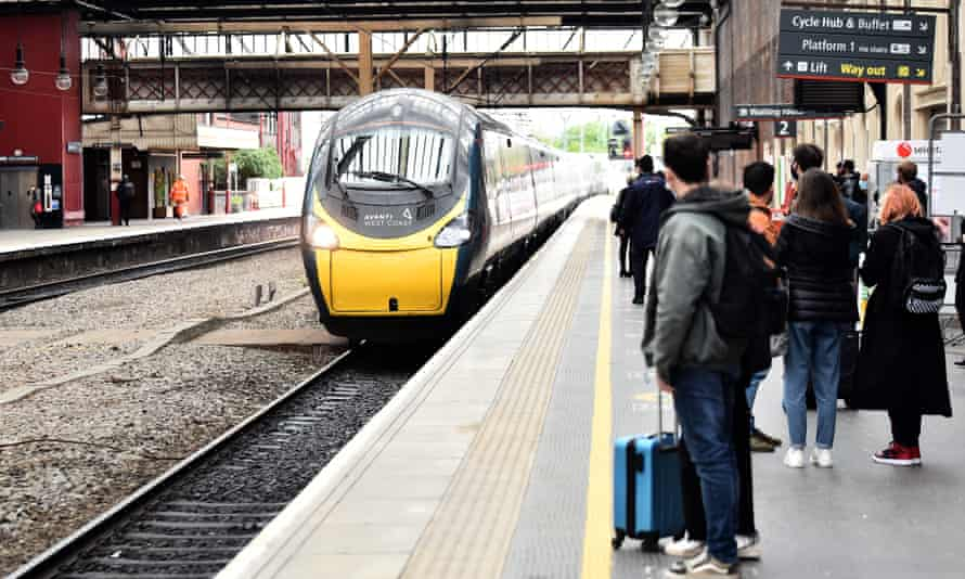 People wait to get on a train at Stoke-on-Trent station.