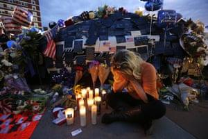 Tasha Lomoglio of Dallas cries after lighting candles in Dallas