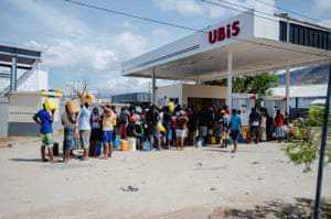 Residents queue for petrol in Roseau. Roads have been congested by fallen trees, hampering the relief effort