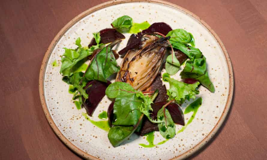 A round plate with green salad leaves, slices of beetroot and a green drizzle