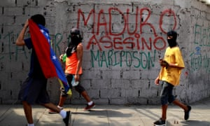 Demonstrators walk past graffiti that reads 'Murderer Maduro'. Washington could widen the sanctions if Sunday's vote goes ahead as planned.
