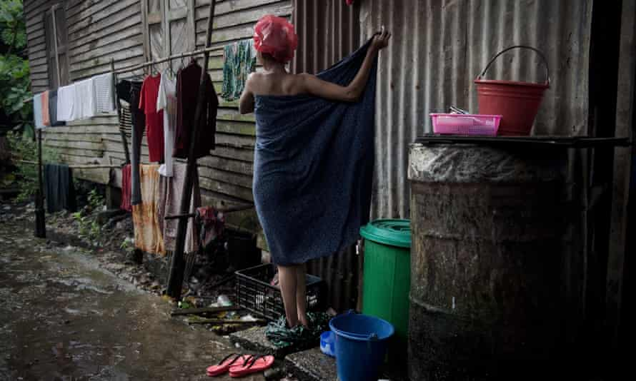 A woman showering outside her shack in Yangon. Women in Myanmar are struggling to gain control of their lives.