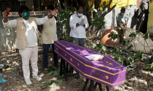 A pastor prays over a coffin of a victim who died from coronavirus at a cemetery in Mumbai, India, 9 June 2020.