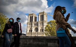 People wearing protective face masks walk near Notre-Dame Cathedral, in Paris.