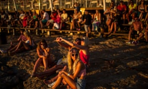 Tourists gather to watch the sunset in front of Cafe del Mar in Sant Antoni near Ibiza, Spain.