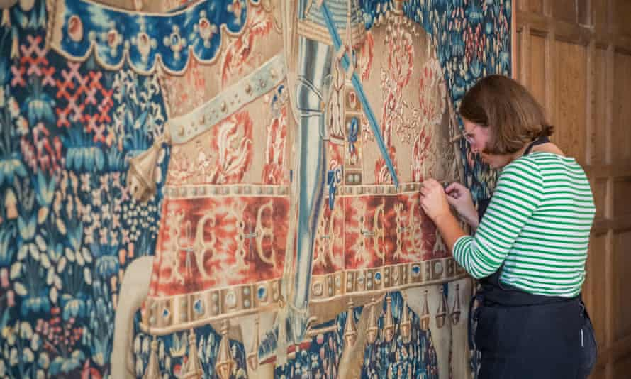 A National Trust conservator checking the tapestry.