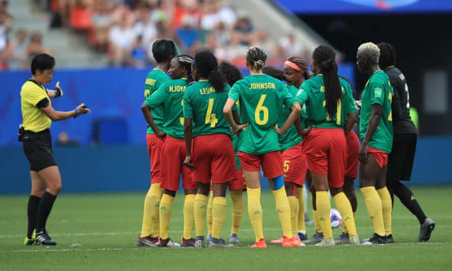 Referee Qin Liang Qin tries to persuade the Cameroon players to play on.