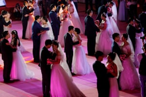Couples kiss during a mass wedding ceremony in Shenyang, China