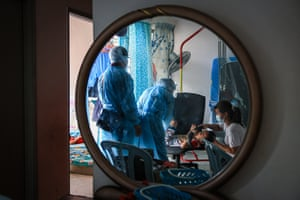 Esther (right) and her son who tested positive for Covid-19, are treated by medical workers at their home in Kuala Lumpur, Malaysia.