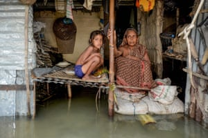A woman and a young girl sit in their flooded house in Sunamganj, north-eastern Bangladesh, on 16 July.