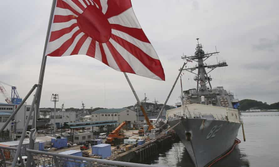 Japan's military Rising Sun flag flutters near a navy ship in this 2014 image. Tokyo rejected South Korea's demand that the flag be removed from vessels taking part in international exercises.