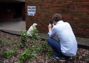 A man photographs his dog outside a polling station at Lillington Gardens community centre in Pimlico, London