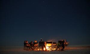 Tourists sit around a bonfire on the Makgadikgadi salt pan, Botswana