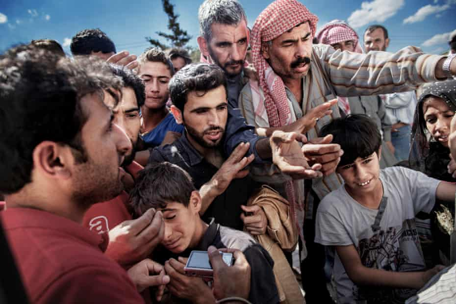 Syrian refugees wait around a truck where a volunteer is distributing water and soap in Akcakale on the border between Turkey and Syria