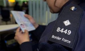 A Border Force officer checks a passport.