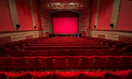 View of a traditional cinema interior with deep red seats, red wall hangings and a red curtain in fromt of the screen
