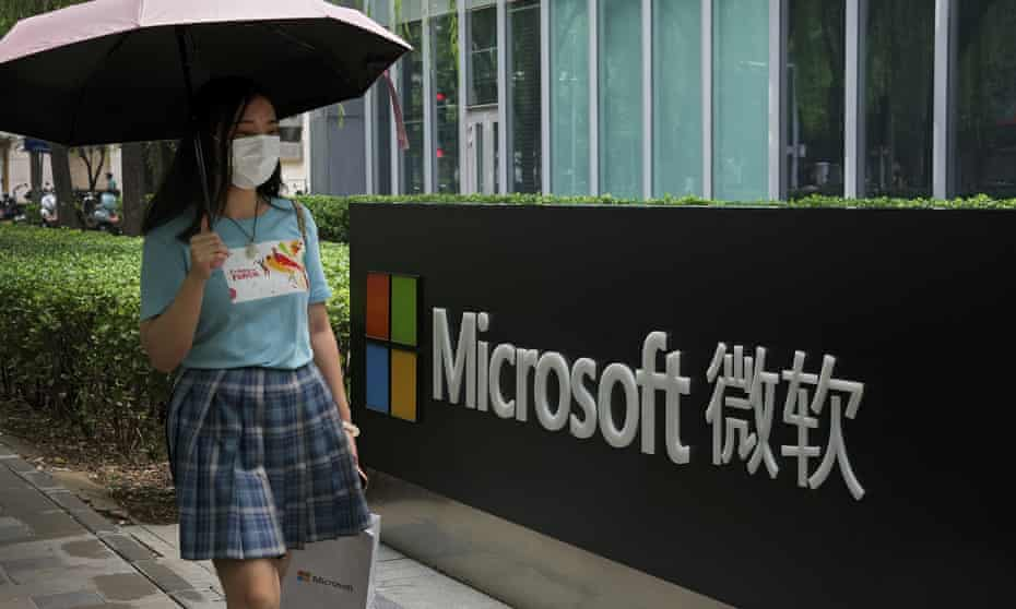 A woman wearing a face mask walks by the Microsoft office building