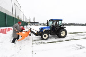 Arsenal ground staff clear snow from the pitches before a training session at London Colney, St Albans