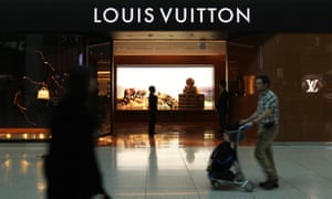 People walk past a Louis Vuitton store at Incheon airport