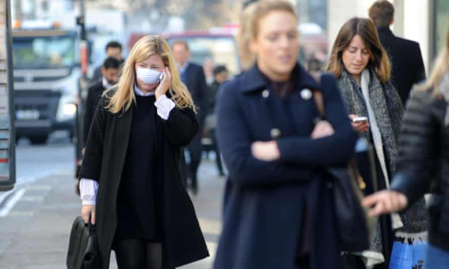 People wearing face masks in London. Air pollution is linked to the early deaths of about 40,000 people a year in the UK.