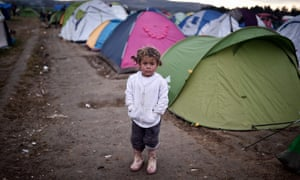 A child stands in a camp for migrants and refugees at the Greek-Macedonian border