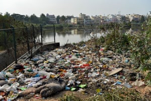 Piles of rubbish accumulate by a lake in Bangalore