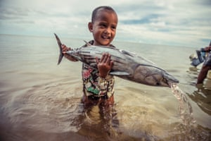A young boy applies all his effort to lifting a 10lb skipjack tuna freshly caught by his father and uncle, Walalung Village, Kosrae Island, Micronesia