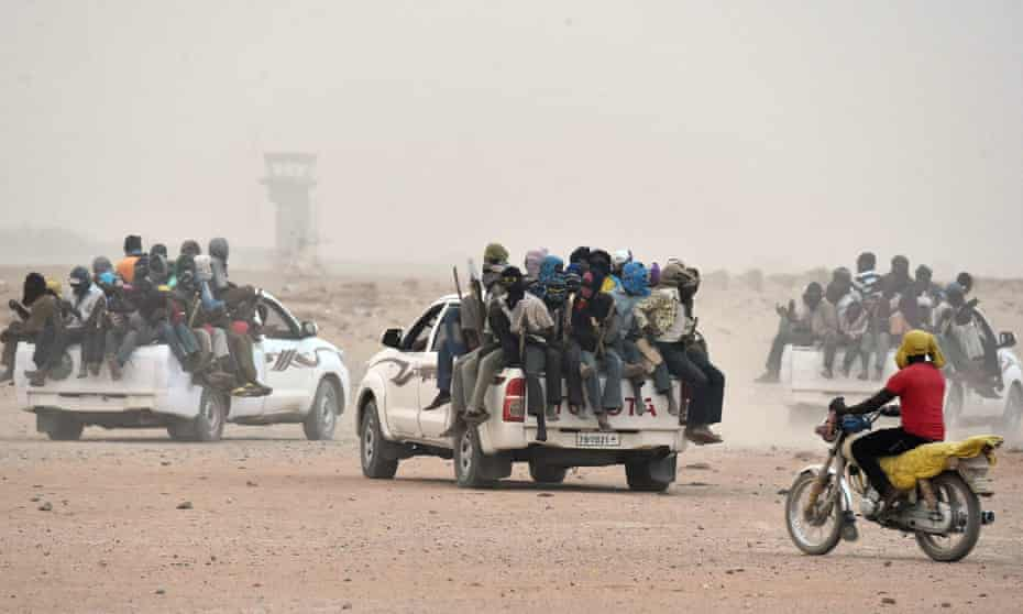 Peoples sit on the open cargo of pick-up trucks, holding wooden sticks tied to the vehicle to avoid falling from it, as they leave the outskirts of Agadez for Libya.