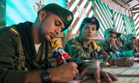 Guerrilla fighters Andrés and Daniela watch videos made by the Farc at a jungle camp.