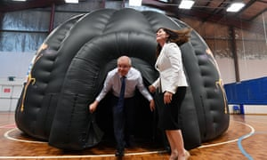 Scott Morrison and the Liberal member for Robertson Lucy Wicks emerge from a Life Education bubble during a cyber bullying announcement at Bateau Bay PCYC Club on the NSW Central Coast in Bateau Bay on Sunday.