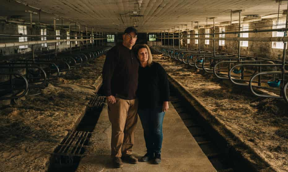 """Ron and Lori Wallenhorst in their empty barn in Cuba City, Wisconsin. """"It's quiet, eerily quiet, for the first time in 50-some years. It's pretty strange,"""" Ron said."""