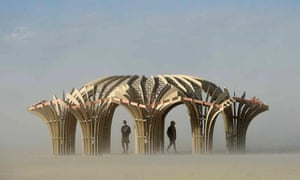 Festivalgoers, or Burners as they're known, stand inside an art sculpture during a dust storm