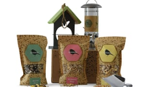 Three packets of bird food and a bird feeder behind