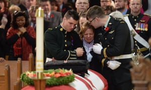 Kathy Cirillo is comforted in front of the coffin of her son Cpl. Nathan Cirillo at his regimental funeral service in Hamilton, Ontario