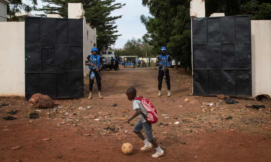 A boy plays football in front of two UN peacekeepers outside Mali's Mamadou Konate stadium during an event organised to promote peace among young Malians.
