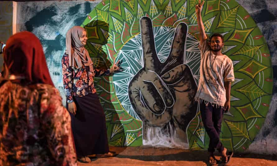Sudanese protesters in front of a recently painted mural.