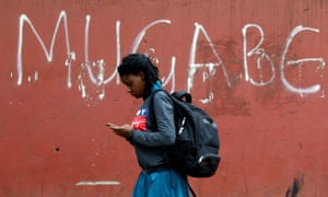 "A woman in Harare walks past a wall with ""Mugabe"" scrawled on it"
