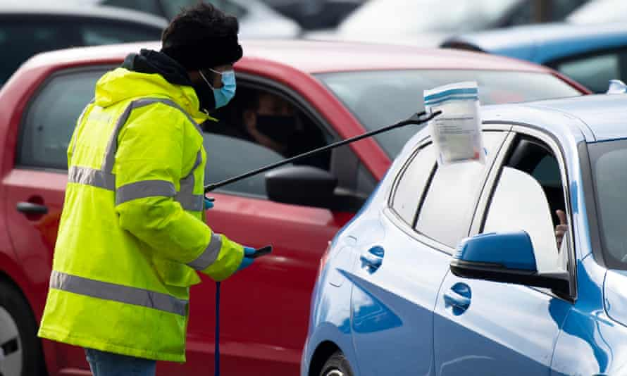 A worker takes a coronavirus test through the window of a car at a temporary coronavirus testing centre  in Bristol, England