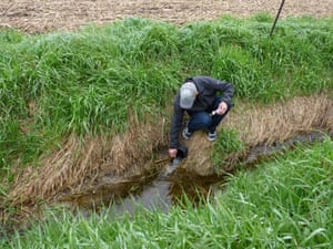 Brent Bierbaum tests the water in a ditch alongside one of his family's fields.