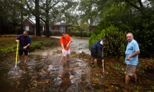 Residents attempt to clear debris from a storm drain as Hurricane Florence comes ashore in Wilmington, North Carolina