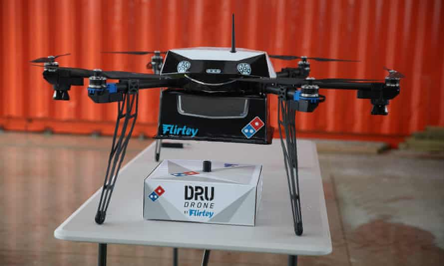 A Domino's pizza delivery drone sits on a table with a pizza box underneath