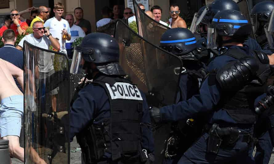 Riot police stand guard