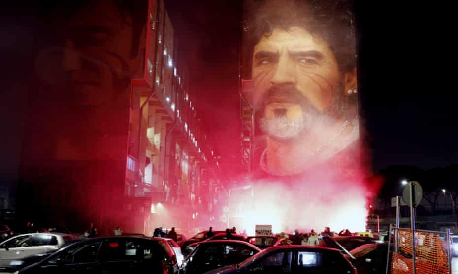 People light flares as they gather under a mural depicting football legend Diego Maradona, in Naples on Wednesday night.