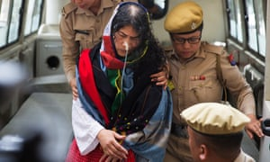 Irom Sharmila is escorted by police officers into a courtroom in Imphal.