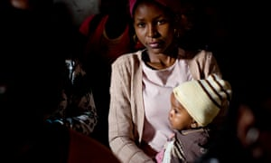 A young mother holds her baby at a community meeting in Kibera