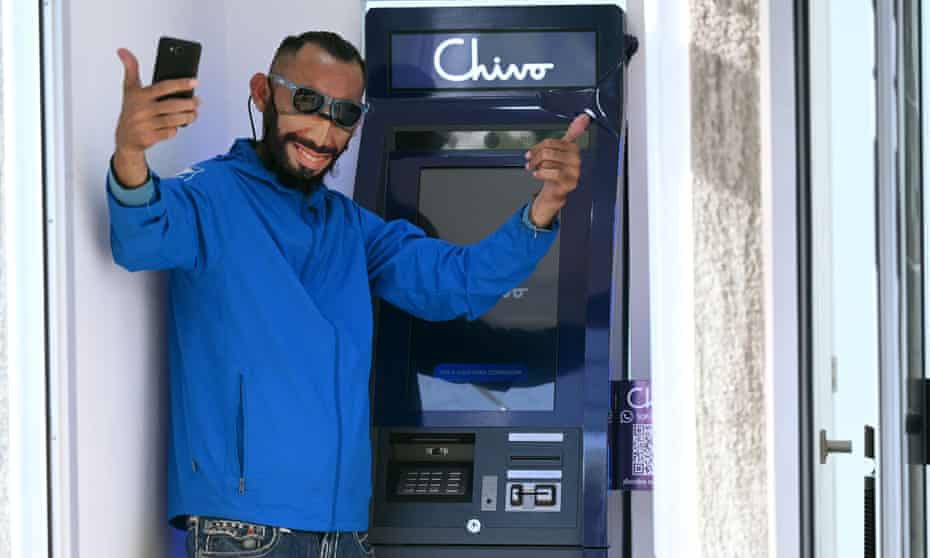 A man wearing a protective face mask with the image of the Salvadoran president, Nayib Bukele, poses for a picture at a bitcoin ATM in San Salvador, on Tuesday.