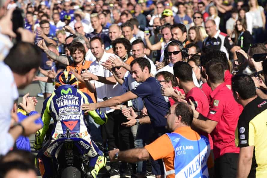Movistar Yamaha's Valentino Rossi is congratulated by spectators on arrival to his pit garage after the race.